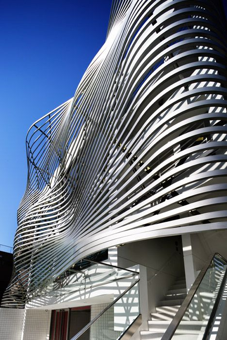 Narrow strips of steel give an undulating facade to this renovated commercial block in Tokyo.
