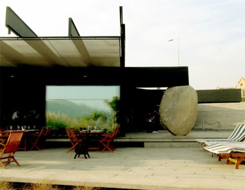Smiljan Radic - Mestizo Restaurant, Santiago 2007 (click for big). The black painted concrete structure is supported by massive boulders. Via.