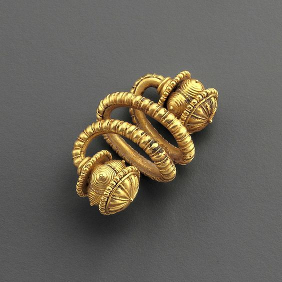 Greek gold spiral , East Greek 7th–6th century B.C. Gold ornaments in a spiral shape are well known throughout the history of Greek jewelry, appearing with either a strictly abstract decoration, as in this early example, or fi tted with animal and even female heads. They are often interpreted as hair ornaments, as they usually do not have a device to fasten them to the earlobe, 4.5 cm long. Private collection