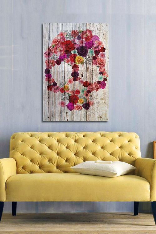 sofá amarelo com quadro de caveira qgrande na parte central da parede. parede cor cinza