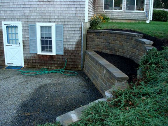 !! Break up retaining wall into two or more sections ... MUCH more attractive.  And lower part could function as seating, too!!!