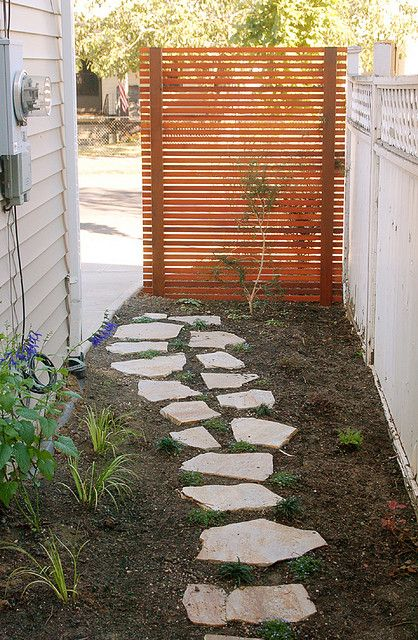 Cedar privacy screen, stepping stone pathway, retaining wall, plant installation.