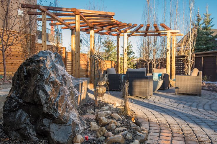 Our clients wanted a natural look for their yard. A cedar pergola and fence border a stone patio that is anchored by a fire bowl, adding a modern counterpoint to the natural textures of the stone and wood. A rock water feature adds to the sights and sounds alongside a variety of trees that surround the patio.