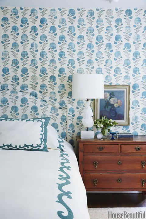 In this master bedroom, walls and headboard upholstered in Jasper's Indian Flower fabric.