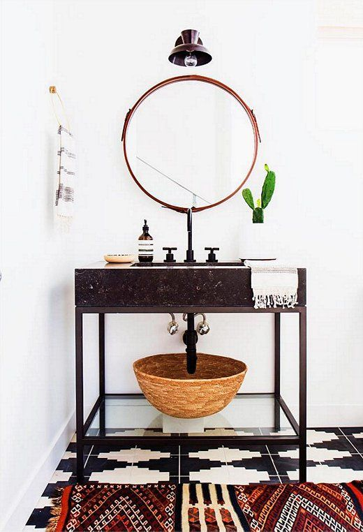 Minimalist bohemian bathroom with round mirror, vintage kilim rug and graphic floor tiles.