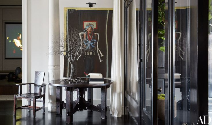 Meg Ryan's SoHo Loft  In a corner of the living room, a painting of Ryan by John Mellencamp overlooks an Arts and Crafts table displaying a Pablo Avilla wire sculpture.