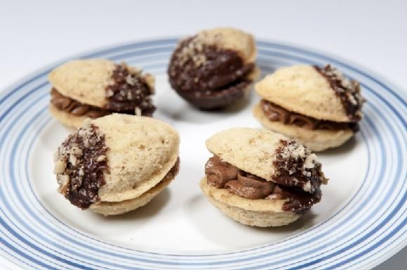 Ořechy plněné krémem zdobené čokoládou a drcenými ořechy  350 g hladké mouky, 150 g moučkového cukru, 120 g vlašských ořechů, 250 g másla