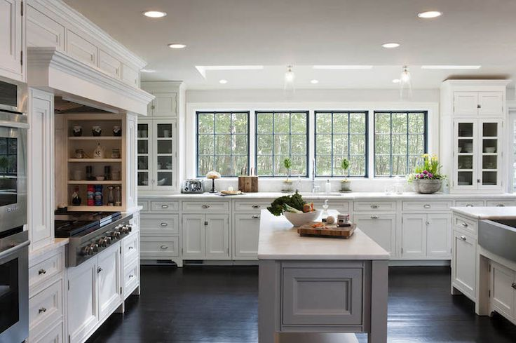 Custom kitchen features a gas stovetop flanked by pull-out spice racks atop honed white marble counters with a paneled vent hood above.