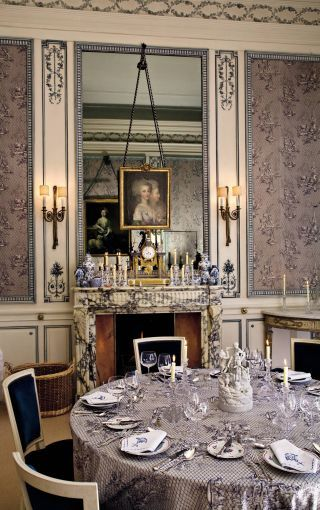 Yester House, Scotland ~ against the mirror is layered delftware and other ceramics, an ornate mantel clock, and a late-18th-century French double portrait previously held in the royal collections at Wiesbaden, Germany.