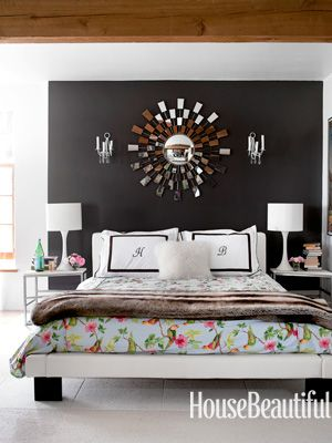 Benjamin Moore's Iron Mountain provides a dramatic contrast to the white leather Licari Design bed and colorful parrot-print coverlet from Studio Due. Design: Deirdre Heekin and Caleb Barber. Photo: Ditte Isager. housebeautiful.com. #bedroom #black #white #sunburst_mirror