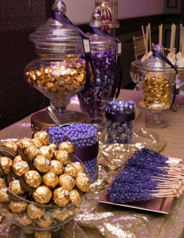 candy-bar-mariage-bonbons-de-taille-différente-enveloppes-dorées-et-violettes-ferrero-rocher-bonbons-rubans-violets-et-nappe-dorée-paillettes