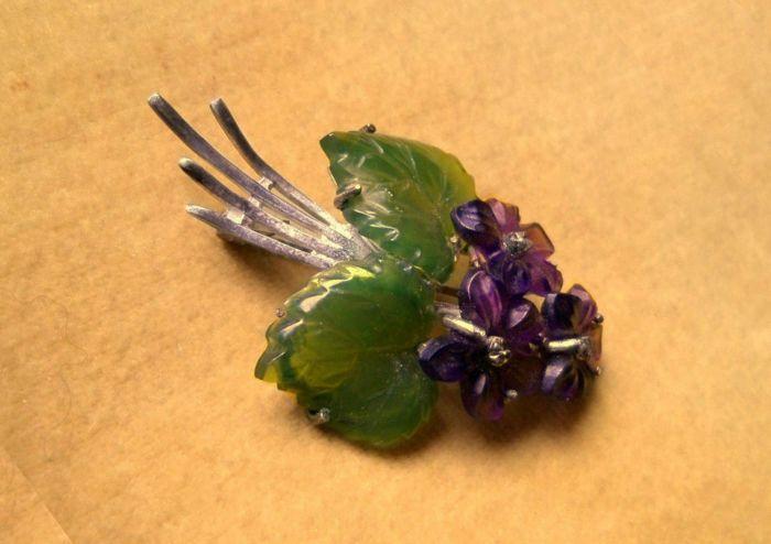 Broche / boeket van bloemen uit amethist bloemen en jade bladeren gemaakt van 835 zilver circa 1950  Mooie oude broche 'boeket van bloemen' met drie paarse Amethist bloemen en Smaragd-groene jade bladeren gemaakt van 835 zilver.De zilveren instelling houdt violette bloemen gemaakt van edelstenen.2 fijn gesneden bladeren gemaakt van groene jade zijn natuurlijk afgebeeld met gekartelde randen en blad aderen.In het centrum van de twee bladeren zijn drie paarse bloemen.De violette bloemen zijn…