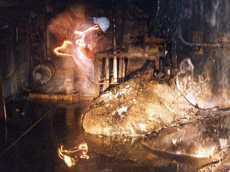 At first glance, it's hard to know what's happening in this picture. A giant mushroom seems to have sprouted in a factory floor, where ghostly men in hardhats seem to be working.  But there's something undeniably eerie about the scene, for good reason. You're looking at the largest agglomeration of one of the most toxic substances ever created: corium.