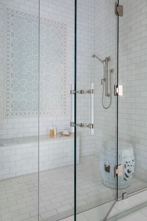 Amazing shower is clad in white marble subway tiles fitted with blue geometric accent tiles over a ...
