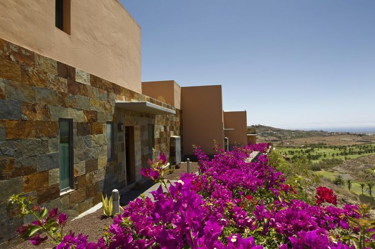 Image of blue sky and the garden of a house www.villagrancanaria.com with Salobre Golf Resort in the background