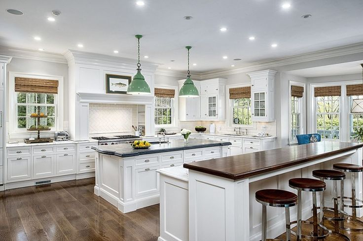 This bright white kitchen is lit by a constellation of embedded ceiling lighting, and features two large islands over natural hardwood flooring.