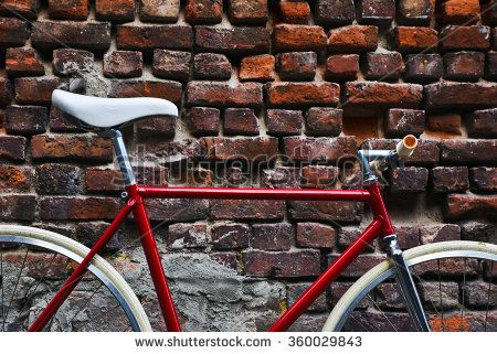 Detail of a red fixie bike, in front of a red brick wall.