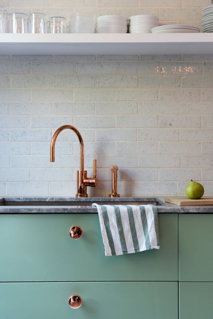 These IKEA cabinets, spotted in the kitchen of a Brooklyn townhouse from Dwell, are paired with a copper faucet and knobs and painted in Farrow & Ball's Breakfast Room Green.