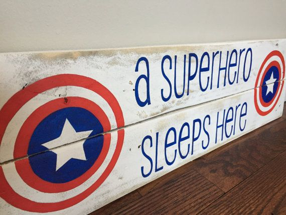 Perfect for any superheros room! Sign is made from recycled wood pallets. Each sign is custom made making each sign unique. The sign pictured: * Measures 24in x 7in. Signs ordered will be made to approximately that size (depending on the wood available) * Captain America symbol (Superhero symbol can be changed - just ask!) * Background is white distressed and the font (a superhero sleeps here) is blue * Hook on the back for easy hanging Last picture was a custom order. If you would like to