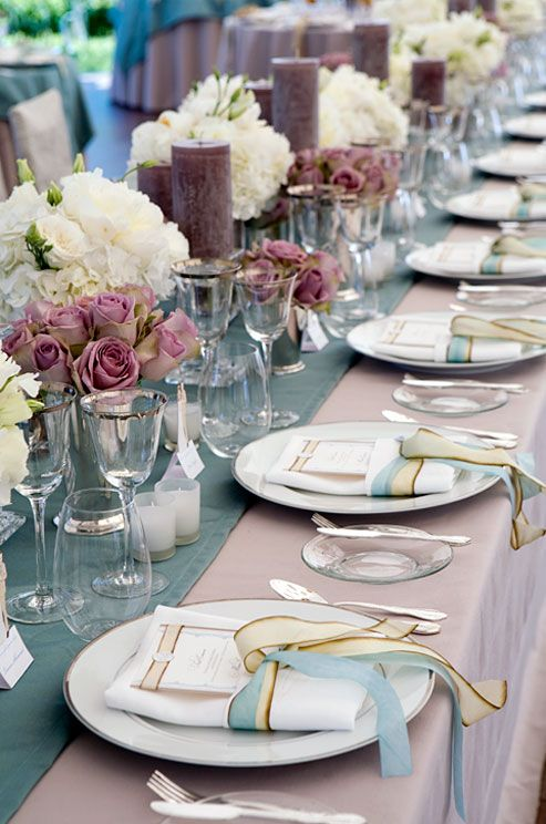 Long tables feature mauve tablecloths with blue runners and dozens of candles and flowers. || Colin Cowie Weddings