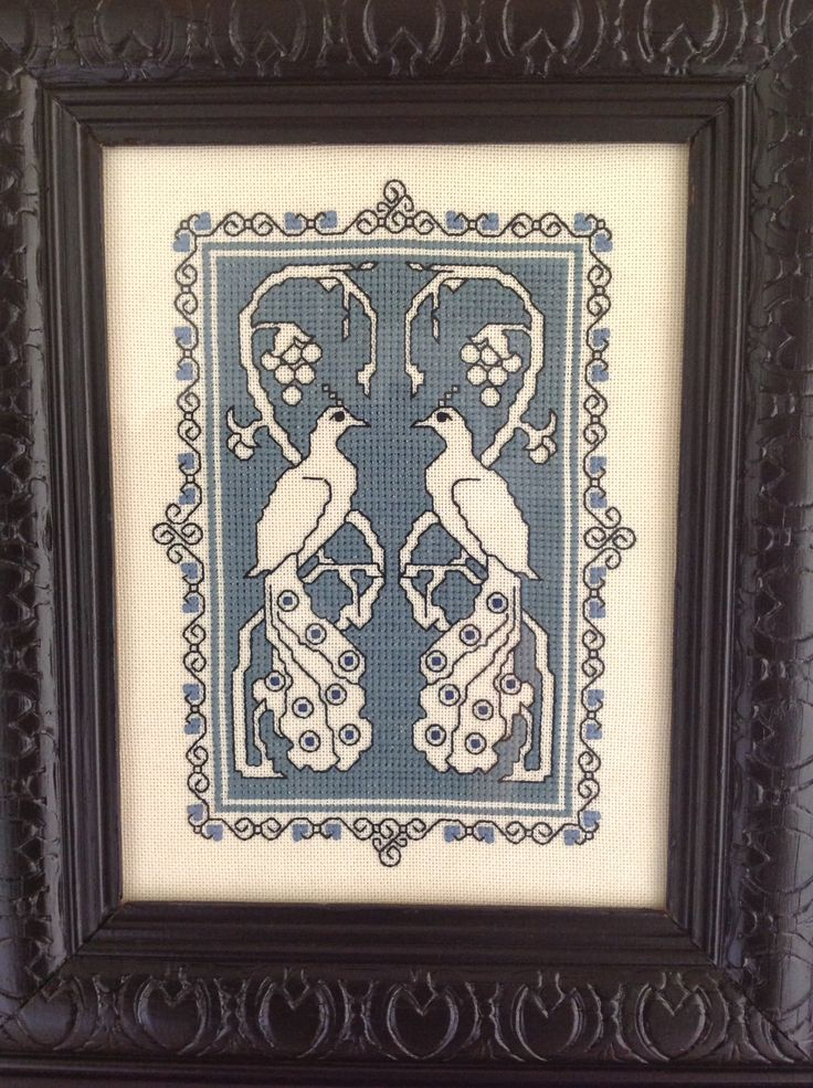 An embroidery I made to celebrate my wedding day. It's a form of cross stitch known as Assisi work. I had it framed in an antique frame I painted black to set the peacocks off.