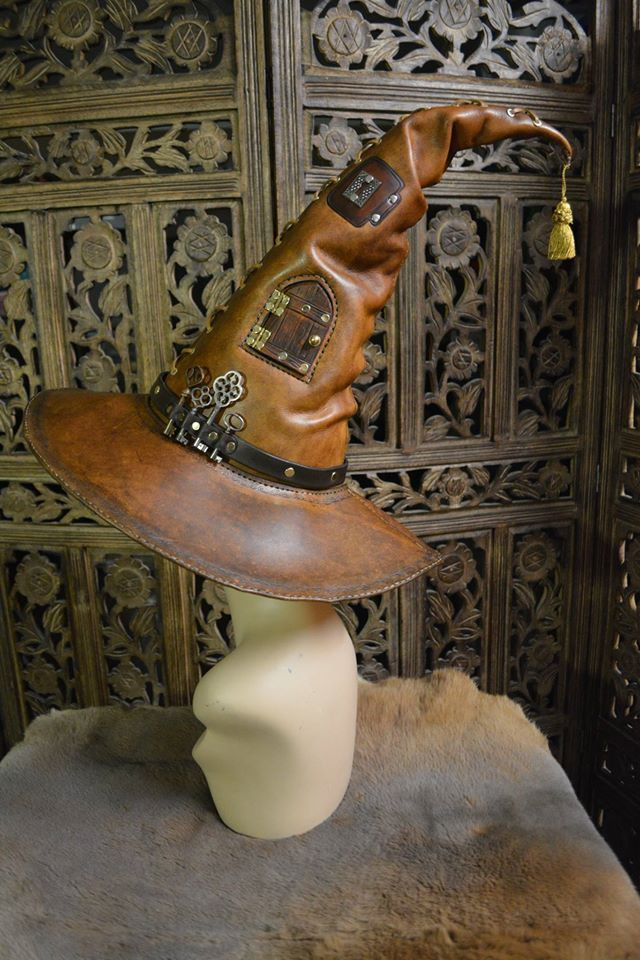A leather hat made for a Portamancer- a wizard specializing in the magic of portals, doors, and extradimensonal spaces.  One of the tooled doors is actually functional, and opens with a brass ...