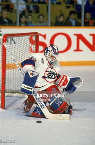 Canadian professional hockey player Bob Essensa, goaltender for the Winnipeg Jets, kneels in front of the goal post as he blocks a puck with his stick during a game with the Toronto Maple Leafs at...