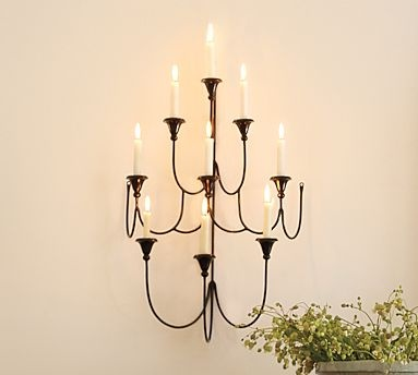 """Add dimension, shape & shadow to a wall. Accented blackened finish, hand-forged iron candelabra cascades in multiple levels &curves, supporting 9taper candles in its cast holders. * 19.5"""" wide x 10"""" deep x 30"""" high * Made of hand-wrought ron with a blackened finish.     * Catalog / Internet Only."""