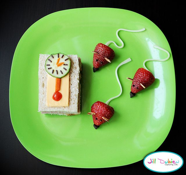 Hickory Dickory Dock  clock - ham and cheese sandwich cut into rectangle, cheese slice on top with a carrot and cherry tomato pendulum. The clock face is a sliced cucumber with spinkles and carrot arms.    mice - strawberries with cheesestring tails, slivered almond ears, sprinkle eyes, and chocolate chip noses.