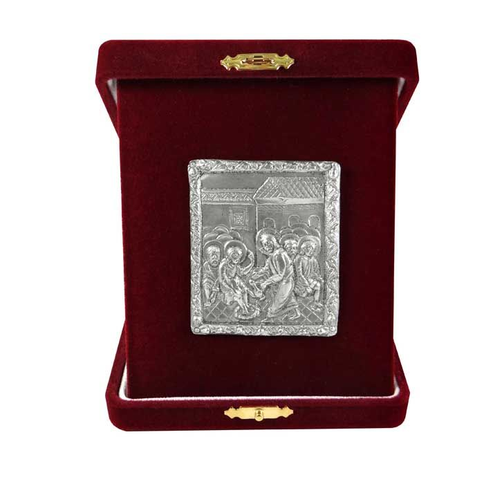 "Icon depicting Jesus washing the Feet of the Apostles, inspired from the cover of a gospel made of silver with local gold plating with central representation of the ""Descent into Hades"", dating around 1693. On the reverse, Saint Sava is depicted with scenes from his life and the Annunciation.  Pure silver 999° icon, placed into a burgundy velvet case. Dimensions icon: 6 cm x 5 cm x 3 cm Dimensions with velvet case: 10,5 cm x 13 cm x 3 cm"