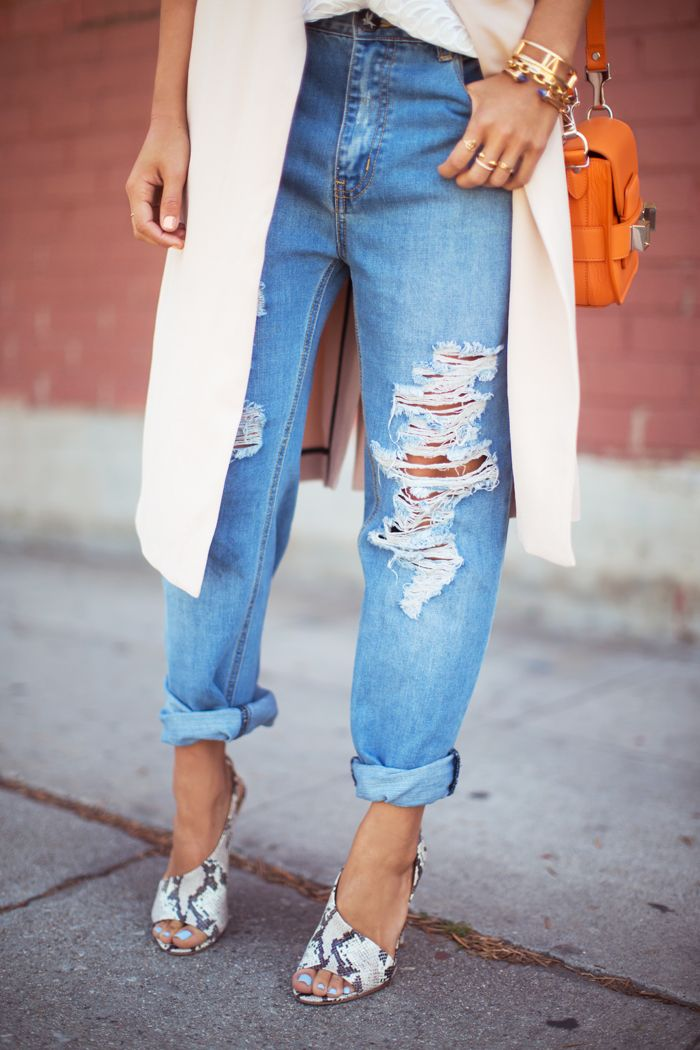 Distressed boyfriend jeans, snakeskin heels, and a long blush best with an orange bag via Song of Style