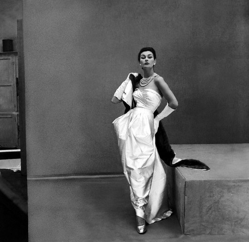 ca. 1951. Model wearing Manguin's white satin gown, mink stole, and pearls.