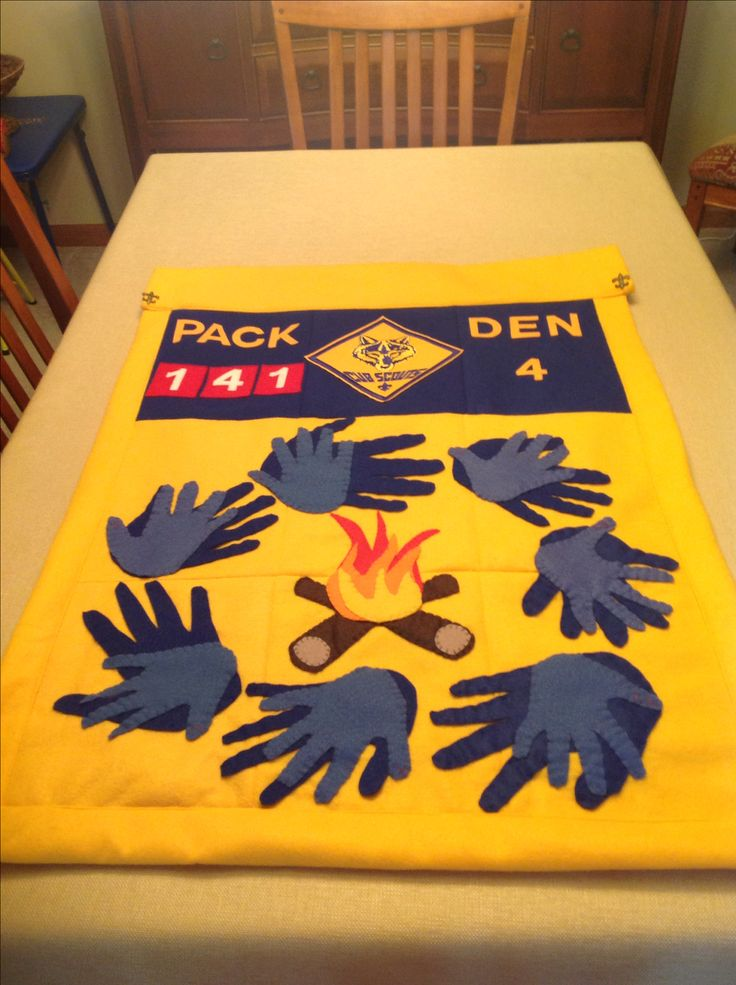 Den flag for Cub Scouts. Parent hand cut-outs overlapped by Cub Scouts