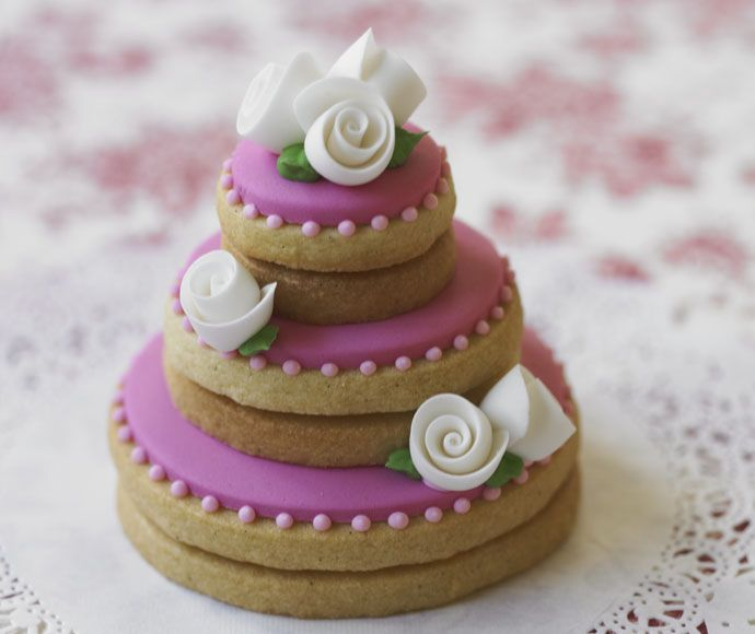 Adorable stacked cookies made to look like a wedding cake and decorated with small flowers.