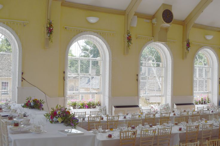 Hanging sheaves of mixed summer flowers between the windows in Corsham town hall