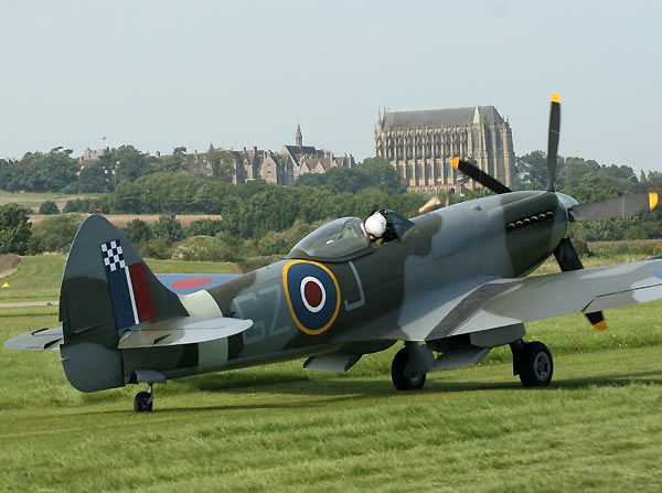 A WWII Spitfire at Shoreham Airport with Lansing Chapel in the background