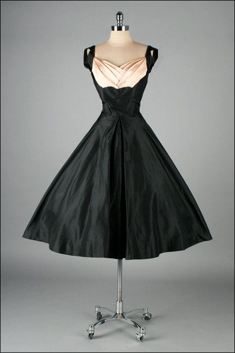 1950's Black and Pink Silk Taffeta.  I just love this style of neckline, and the huge skirt, but I don't know if I'd ever wear it.  Maybe if it had a cousin that was a wrap dress.  I can't stand girdles, and you'd need some serious underthings for this!