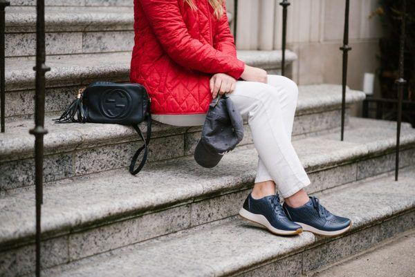 Луки и блестки носить случайный выходные наряд с красной куртке, Gucci сумки, белые джинсы, бейсбол шляпы и кожаные кроссовки.
