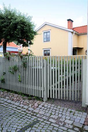 3. Spjälgrind – Samma form som staketetSmala virkesbrädor har format husets inhägnad. Grinden är nästan svår att upptäcka då den är tillverkad av samma dimensioner som staketet. Fyrkantsgatstenen nedanför markerar entrén. Grinden är monterad med ett Z på baksidan, ett klassiskt sätt att med snedsträva hålla grinden rät. Grind och staket är målat i en behaglig grågrön nyans.