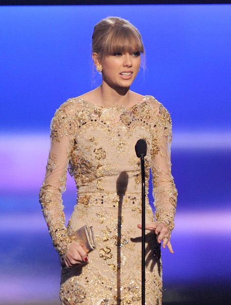 "Taylor Swift on stage at the AMAs with Lauren Merkin's ""Essex"" clutch."
