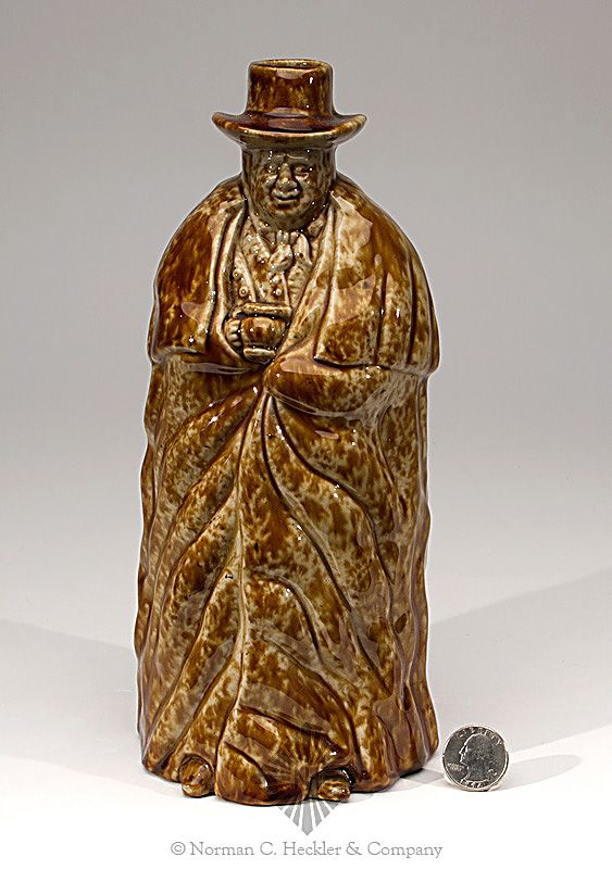 Bennington Pottery Coachman Bottle, Bennington Pottery, Bennington, Vermont, circa 1849. In the form of a coachman with a heavy cloak holding a mug to his chest, tan and brown flint enamel glazes, ht. 10 inches; (right boot has resin repair). Similar in form to Barret plate 419, left Displays well. Attractive colored glaze. #Bottles #Antique #MADonC