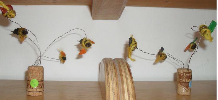 Bijen van elzenpropjes. Gele wol, bijenwas vleugels, kurk als houder en ijzerdraad om ze te laten vliegen.