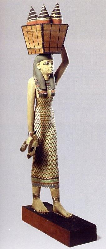 Portadora de ofrendas, Reino Medio, XI Din. El Cairo, Museo Egipcio. La mujer personifica una propiedad que habría proporcionado ofrendas de alimento para el espíritu de Meketre para la eternidad. Lleva un pato vivo cogido por las alas en una mano y equilibra una cesta de alimento con la otra. Su vestido se decora con el diseño de pluma a menudo asociado con diosas, y esto puede referirse a Isis y Nephthis, que protegen el espíritu del difunto en la otra vida.