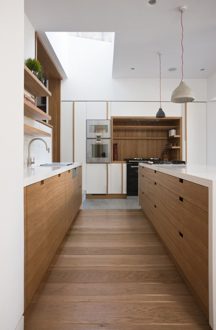 """""""We installed a wood floor in the actual kitchen area because wood is a more accommodating material to stand on for any period of time than concrete,"""" Legge says. A skylight brings daylight from above into the one story part of the remodel."""