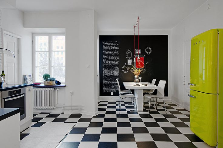 Black-and-white floor, chalkboard wall. Love this eat-in kitchen. (Though I can't stand the color of the fridge. Would love to see it in a bright red or hot pink.)