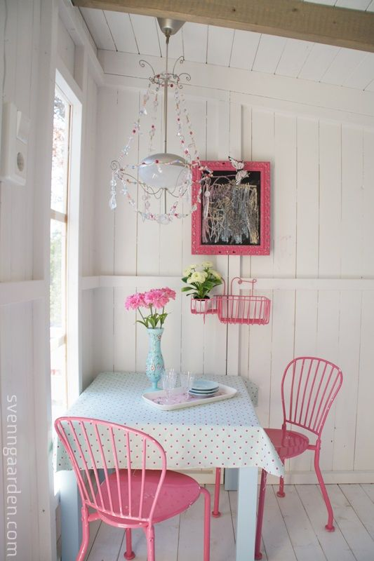 Pink chairs in a simple rustic white kitchen. Photo proof that a Chandelier can look terrific anywhere.