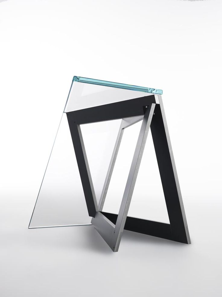 """QUADROR 01 / Design: Dror, 2015 / While working on the construction of a frame composed of two surfaces intersecting each other, Dror """"stumbled"""" on a fascinating discovery: expertly cut and combined together the material Creates a new form, a new structural element which, when open, creates a stable and independent triangular base. In QuaDror 01 this base is enhanced and complemented by a """"dress"""" in extraclear tempered glass."""
