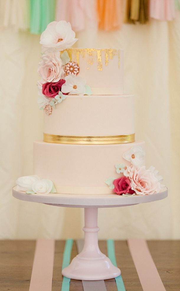 Gold and pink wedding cake with flower accent decorations.