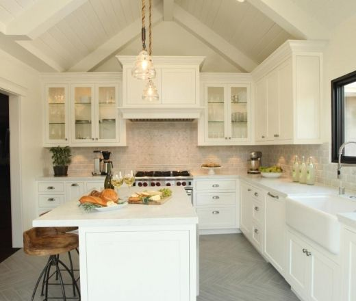 This modern farmhouse kitchen has valulted ceilings and light colored  finished which give the moderately sized