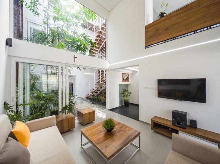 Sala de estar moderna com um teto alto ao lado de um jardim pequeno do pátio, Nellikunnu, Thrissur, estado de Kerala, India [2000 × 1497]